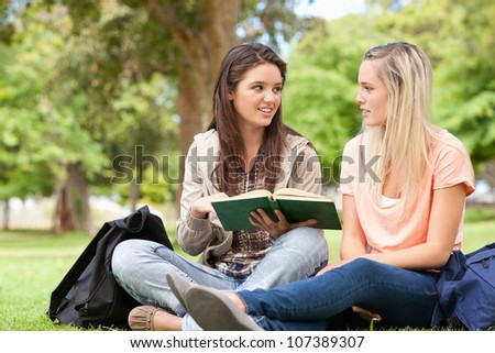 Female teenagers sitting while studying with a textbook in a park - stock photo