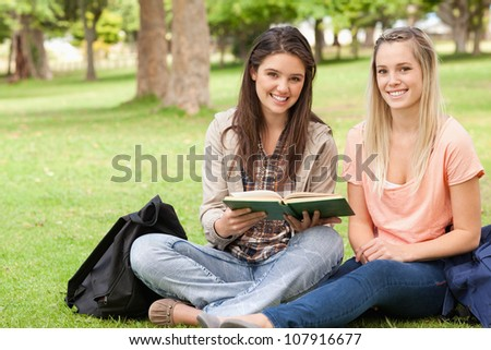 Female teenagers sitting with a textbook in a park while looking at camera - stock photo