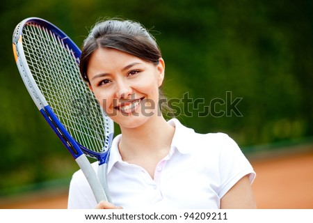 Female tennis player holding a racket and smiling - stock photo