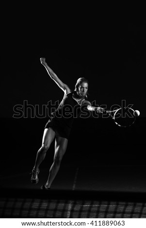 Female Tennis Player With Racket Ready To Hit A Tennis Ball - Isolated On Black - stock photo
