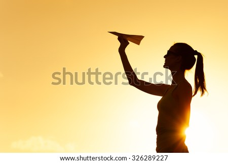 Female throwing paper airplane.  - stock photo
