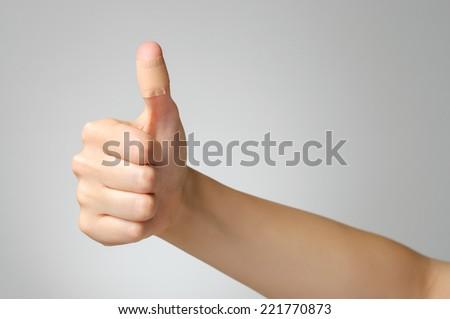 Female thumb with adhesive bandage - stock photo