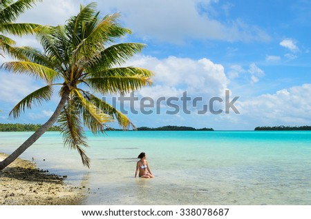 Female tourist bathing in the shallow water of the sea under a hanging palm tree on a beach on a desert island in the lagoon of Rangiroa, a tropical atoll near Bora Bora in pacific  French Polynesia. - stock photo