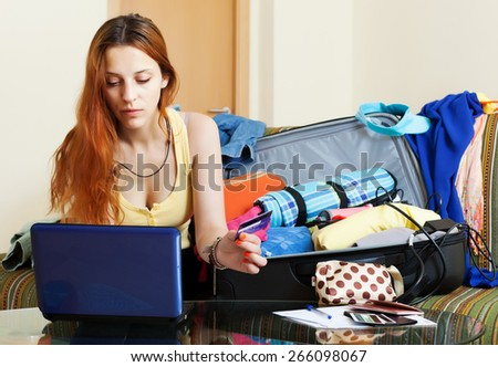 Female tourist buying tickets or reserving hotel online - stock photo