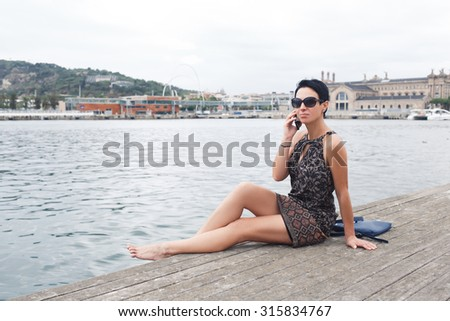 Female tourist having mobile phone conversation while sitting on a river jetty against beautiful landscape background with copy space, modern woman talk on cell telephone while enjoying leisure time  - stock photo