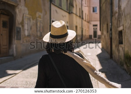 Female tourist in Europe wearing hat and scarf - stock photo