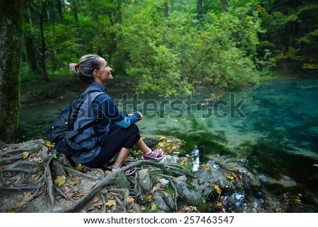 Female tourist in the forest resting - stock photo