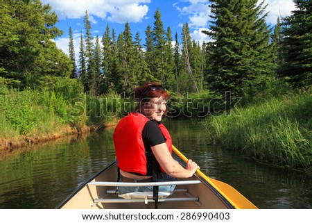 Female tourist paddling a canoe on the mountain lake and blurred green wood in the background. Vermilion Lakes. Banff National Park, Alberta, Canada) - stock photo