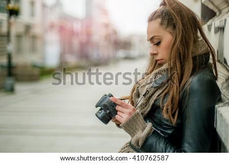 Female Tourist Photographer. Pretty young female tourist photographer taking pictures in the city - stock photo