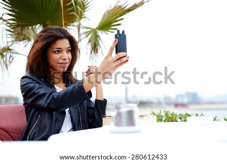 Female tourist using mobile phone camera for take a picture of herself during vacation holidays in Barcelona, stylish afro american woman taking self portrait with smart phone, feeling good and happy - stock photo