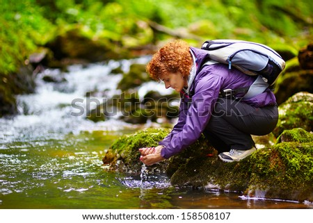 Female tourist washing hands in a mountain river - stock photo