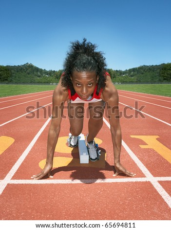Female track athlete poised at starting line - stock photo