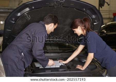 Female trainee mechanic at work - stock photo