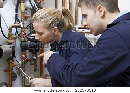 Female Trainee Plumber Working On Central Heating Boiler - stock photo