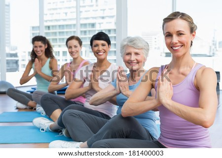 Female trainer and class sitting with joined hands in a row at yoga class - stock photo