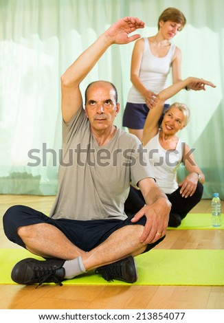Female trainer and mature couple worming up at gym  - stock photo