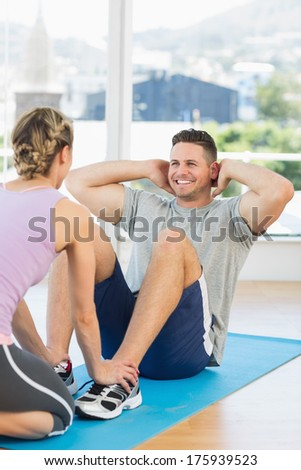 Female trainer assisting fit man in doing sits up at fitness club - stock photo