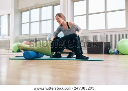 Female trainer instructing senior woman going exercise on a foam roller. Elder woman doing pilates workout with personal instructor at gym. - stock photo