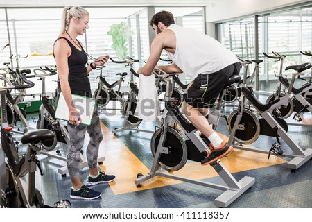 Female trainer looking at stopwatch and man using exercise bike at the gym - stock photo
