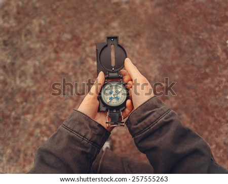 Female traveler holding a compass on nature. Point of view shot - stock photo