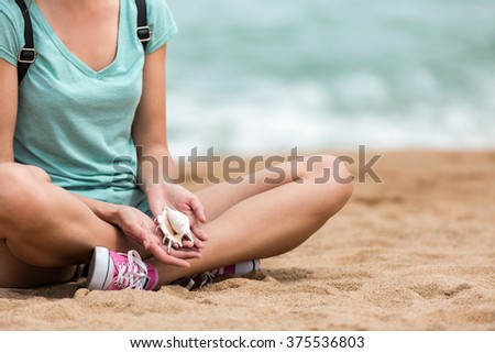 Female traveler relaxing on seashore, holding conch seashell - stock photo