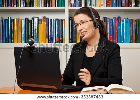 Female tutor or teacher with headset, computer and camera in her office talking with a student via video telephony, skype - stock photo