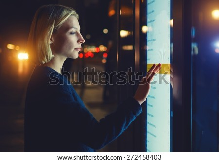 Female using automated teller machine with big digital screen while standing in night city out-of-focus lights,woman verifies account balance on banking application via modern device, filtered image - stock photo