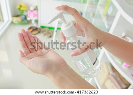 Female using hand press bottle and pouring alcohol-based sanitizer on other hands. Apply all path body. - stock photo