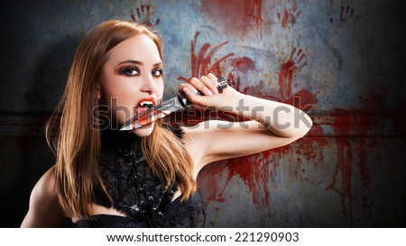 female vampire with a knife in front of a bloody wall - stock photo