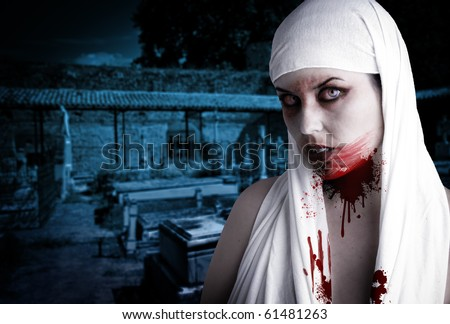 Female vampire with blood stains in a cemetery. Gothic Image halloween - stock photo