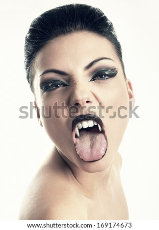 Female vampire with open mouth and large fangs - stock photo