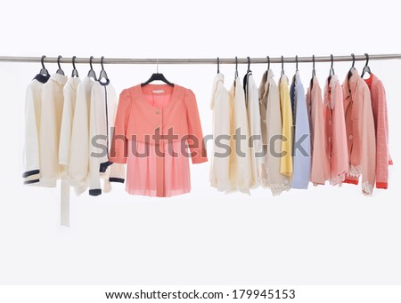 Female Variety of colorful clothes hanging on the rack - stock photo