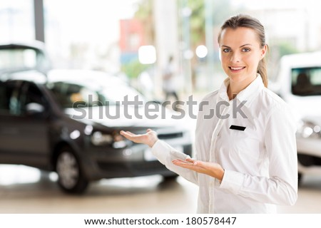 female vehicle sales consultant presenting new cars at dealership - stock photo