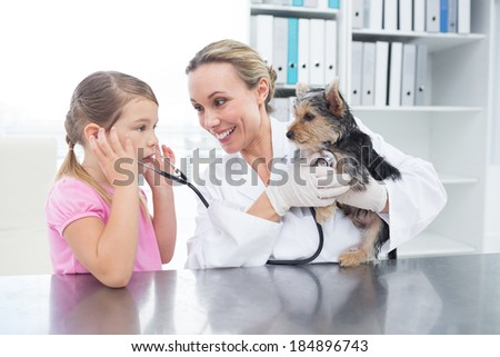 Female vet with girl examining puppy in clinic - stock photo