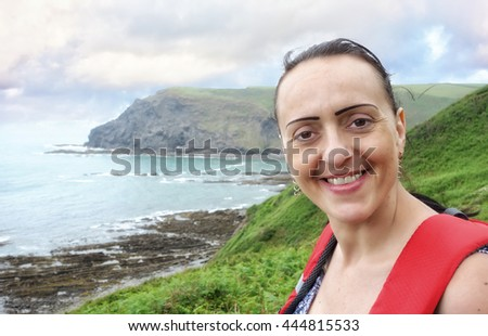 female walker on the coastal path in Devon, England, UK. - stock photo