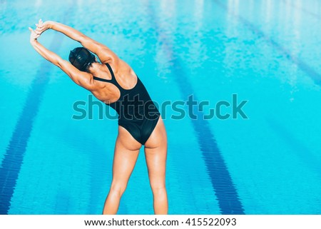Female warming up for swimming. Stamding on pool edge and warming up hands and shoulders - stock photo