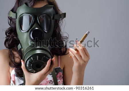 Female wearing a gas mask for protection against the cigarette smoke - stock photo