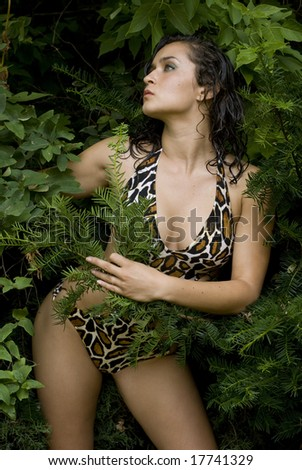 Female with animal print swimsuit posing in green bushes - stock photo