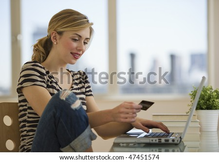 female with credit card shopping on-line from home - stock photo