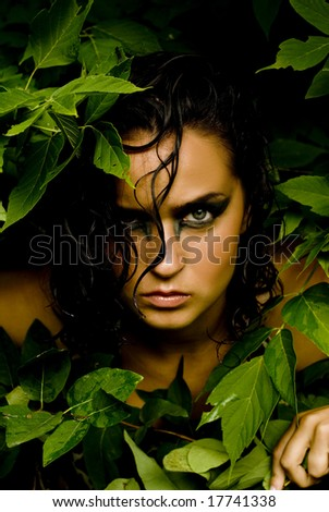 Female with dark eye shadow posing with leaves framing her face - stock photo