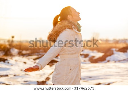 female with outstretched winter arms - stock photo