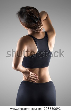Female with pain back pain and neck pain, Isolated over grey background - stock photo