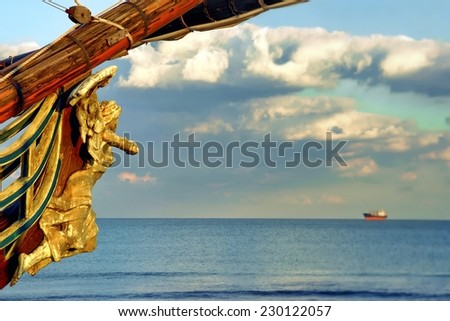 Female Wooden Carved Figurehead found at the Prow of Old Ship. Modern ship at sea horizon. - stock photo