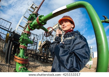 Female worker in the oil field talking on the radio wearing orange helmet and blue work clothes. Industrial site background. - stock photo
