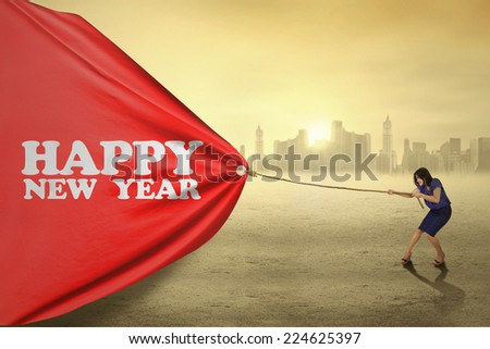 Female worker pulling a big banner of new year in the morning - stock photo