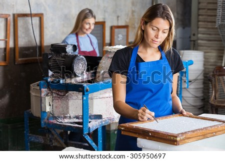 Female worker using tweezers to clean paper on mold in factory - stock photo