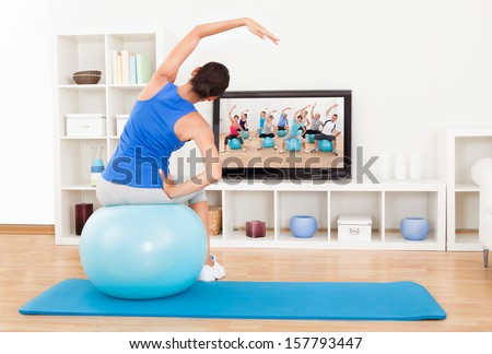 Female Working Out With An Blue Exercise Ball In Front Of Television - stock photo