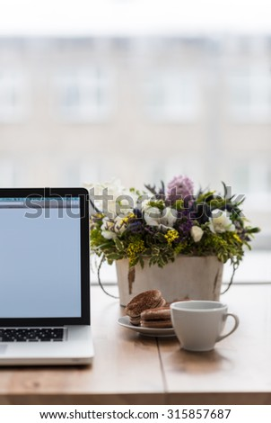 Female workplace with laptop, flowers and coffee - stock photo