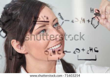 female writes out a chemistry equation. - stock photo