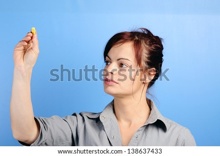 female writing something on glass board with chalk - stock photo